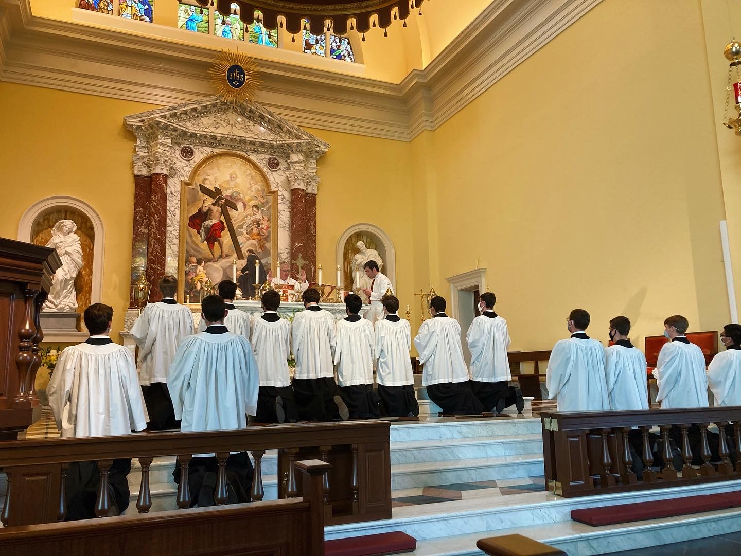 Altar servers kneeling during the celebration of the liturgy of the Eucharist in Holy Cross Chapel. / Jimmy Mitchell