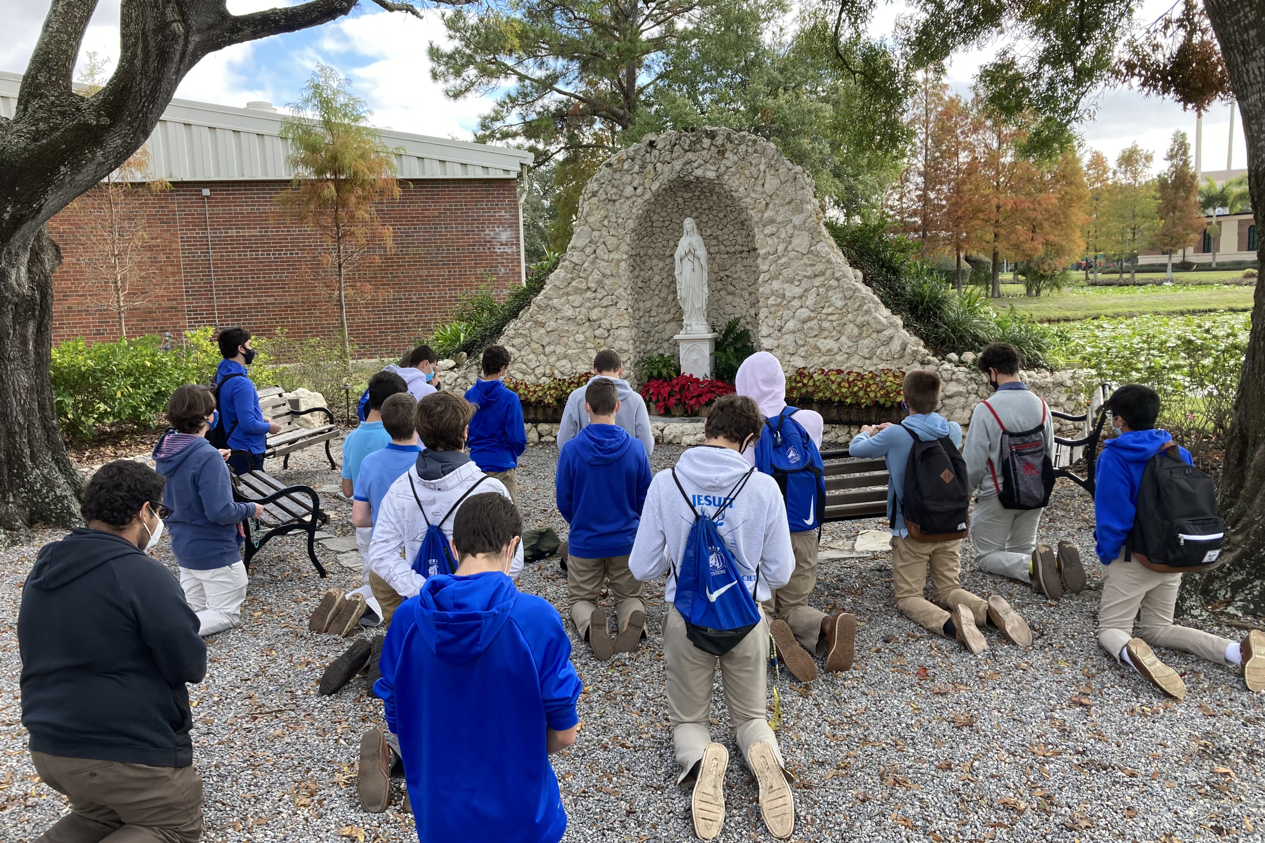 A group of students from Jesuit High School, an all-boys school in Tampa, Florida, praying in front of a statue of Our Lady.